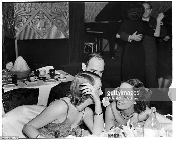 Actress Merle Oberon laughs at a table with friends during an event in Los Angeles California