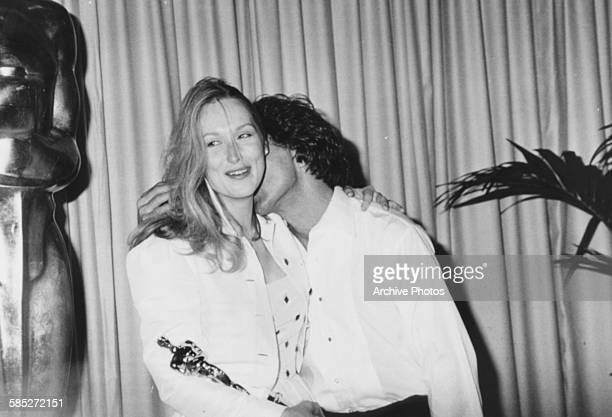 Actress Meryl Streep holding her Oscar award for the film 'Kramer vs Kramer' and being kissed on the neck by costar Dustin Hoffman at the 52nd...