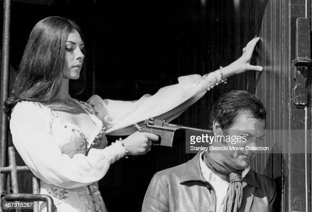 Actress Michele Mercier holding a gun to the head of actor Tony Curtis in a scene from the movie 'You Can't Win 'Em All' 1970