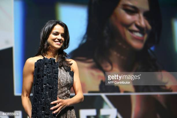 US actress Michelle Rodriguez holds the achievement tribute award she received before the screening of the movie 'Zookepper's wife' on September 7...