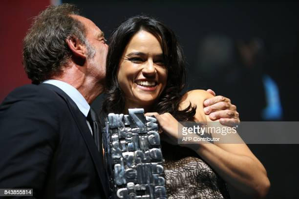 US actress Michelle Rodriguez holds the achievement tribute award she received from French actor Vincent Lindon during a ceremony before the...