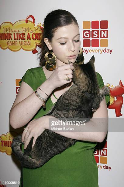 Actress Michelle Trachtenberg holds a cat as she arrives at the Meow Mix Think Like a Cat Game Show Premiere on November 12 2008 in Los Angeles...