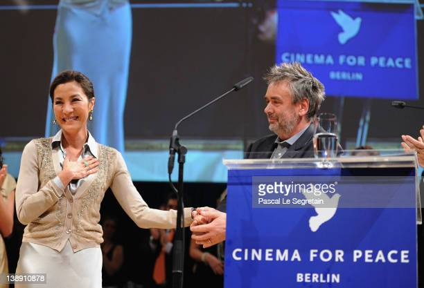 Actress Michelle Yeoh reacts onstage with director Luc Besson as they receive the International Human Rights Film Award for 'The Lady' at the Cinema...