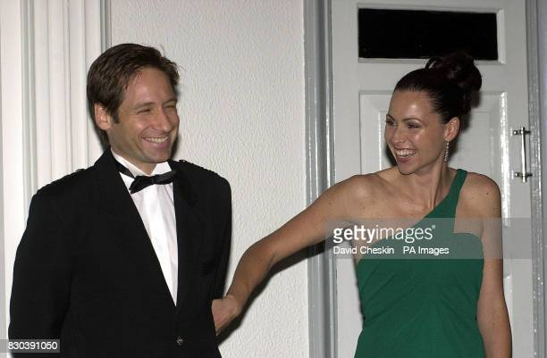 Actress Minnie Driver and American actor David Duchovny share a joke as they attend the premiere of their film Return to Me attended by the Prince of...