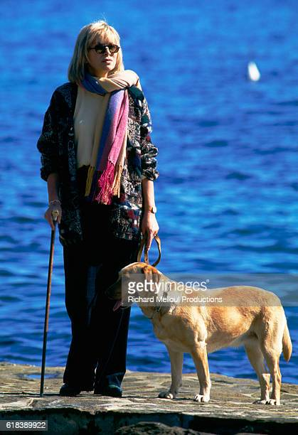 Actress Mireille Darc relaxes with her dog on the French Riviera during the filming of her television series Les Coeurs Brules