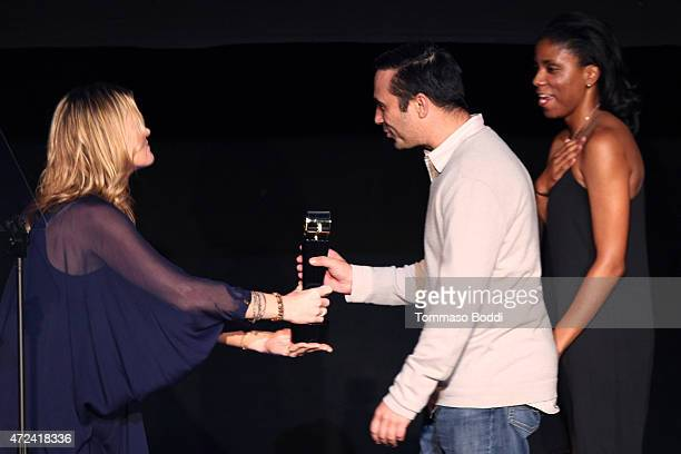 Actress Missi Pyle honors the winners of the Golden Fleece Golden Trailer Award producer Dave Ligorner and editor Meko Winbush on stage at the 16th...