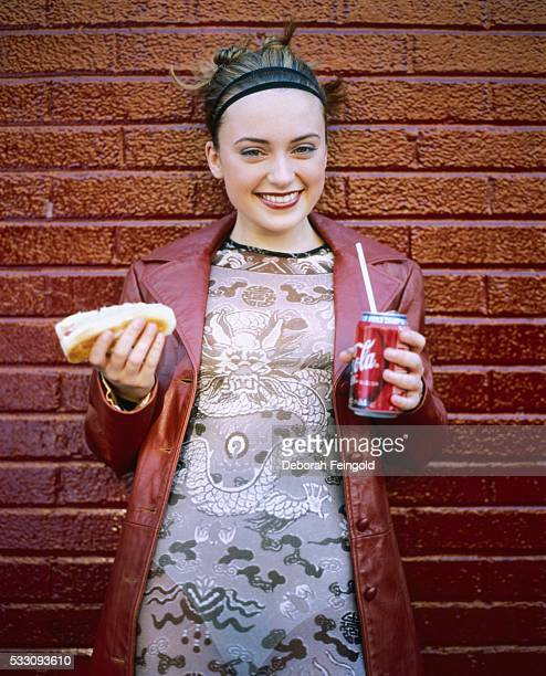 Actress Monica Keena stands next to a brick wall and holds a hot dog in one hand and a CocaCola can in the other