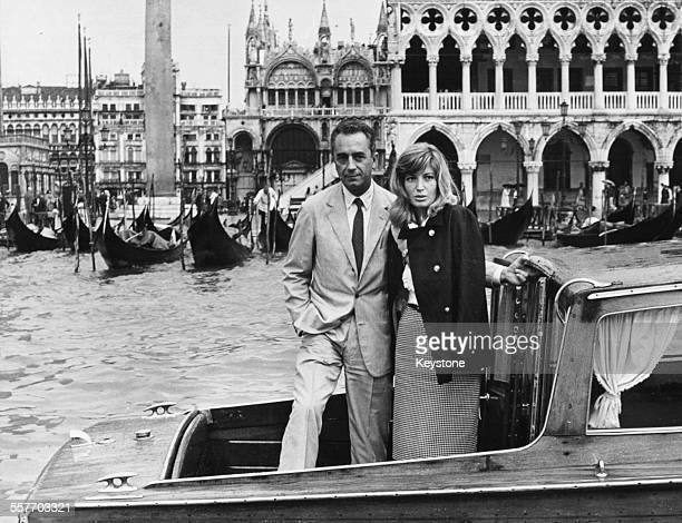 Actress Monica Vitti and director Michelangelo Antonioni standing on a boat as they attend the International Film Festival Venice September 1962
