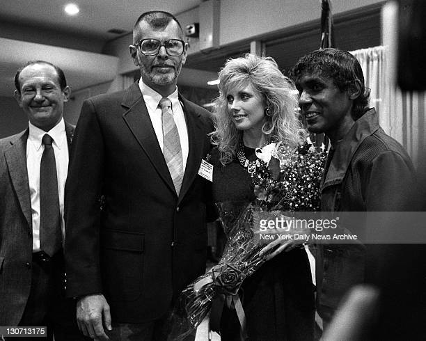 Actress Morgan Fairchild accepts bouquet of roses from AIDS patients Bernard Braverman and Hector Sabat as Veterans Administration Hospital opens a...