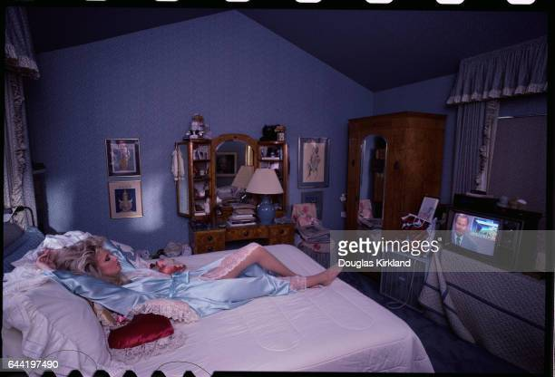 Actress Morgan Fairchild wears a light blue negligee while lying on her bed watching television
