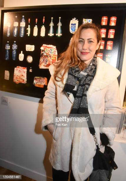 Actress Myriam Charleins poses with a picture of Brigitte Bardot's dustbin contents during Paparazzi Bruno Mouron et Pascal Rostain Exhibition...