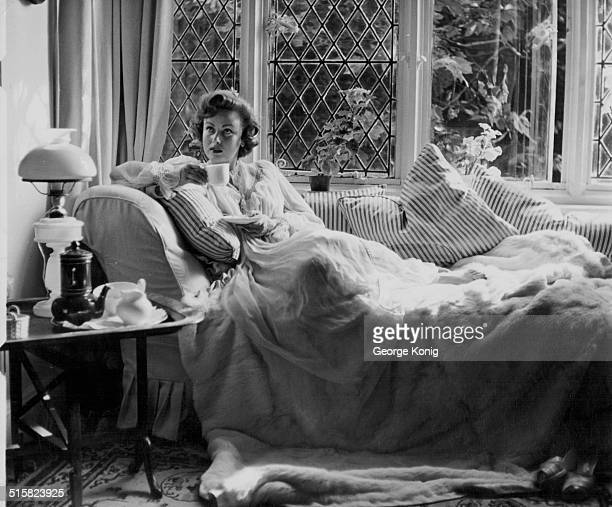 Actress Nadia Gray relaxing with a morning coffee and and a bear skin rug and cushions at her home in Chelsea London circa 1955