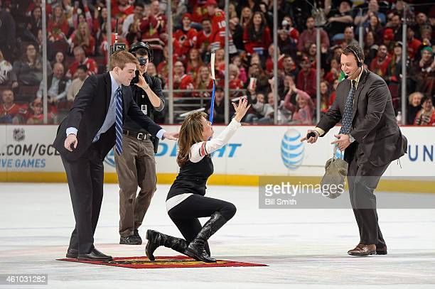 Actress Nancy Lee Grahn loses her balance after shooting the puck in between periods of the NHL game between the Dallas Stars and the Chicago...