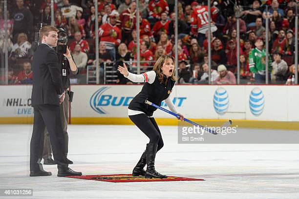 Actress Nancy Lee Grahn reacts after shooting the puck in between periods of the NHL game between the Dallas Stars and the Chicago Blackhawks at the...