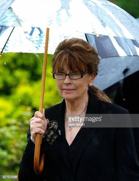 Actress Nanette Newman arrives under an umbrella to attend the funeral of Sir John Mills at the church of St Mary The Virgin in Denham 27 April 2005...