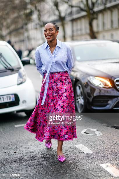 Actress Naomi Ackie wears a mauve shirt, a red and pink floral print skirt, pink pointy Valentino shoes, outside Valentino, during Paris Fashion Week...
