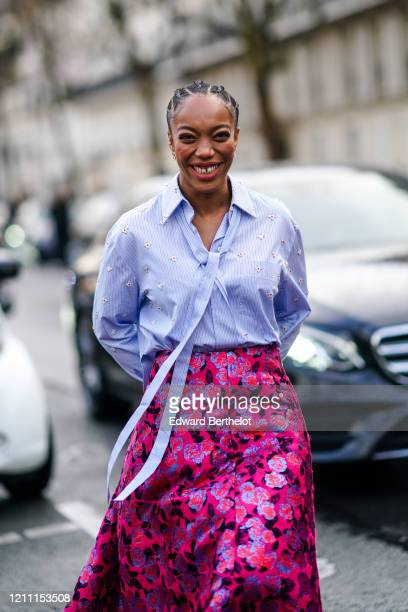 Actress Naomi Ackie wears a mauve shirt a red and pink floral print skirt outside Valentino during Paris Fashion Week Womenswear Fall/Winter...