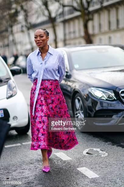 Actress Naomi Ackie wears a mauve shirt a red and pink floral print skirt pink pointy Valentino shoes outside Valentino during Paris Fashion Week...