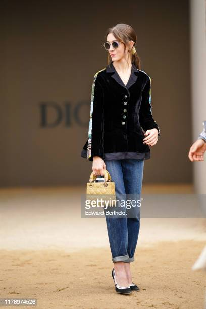 """Actress Natalia Dyer who portrays the character """"Nancy Wheeler"""" in the Netflix series """"Stranger Things"""", wears sunglasses, a black top with printed..."""