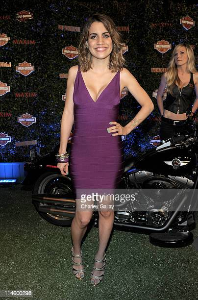 Actress Natalie Morales turns the key on a HarleyDavidson to raise money for Harley's Heroes at the 2010 Maxim Hot 100 Party held at Paramount...