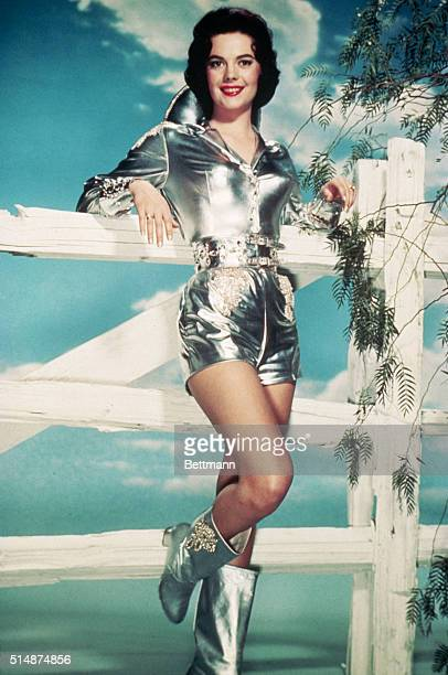 Actress Natalie Wood leans against a studio fence in a short silver lame Western ensemble.