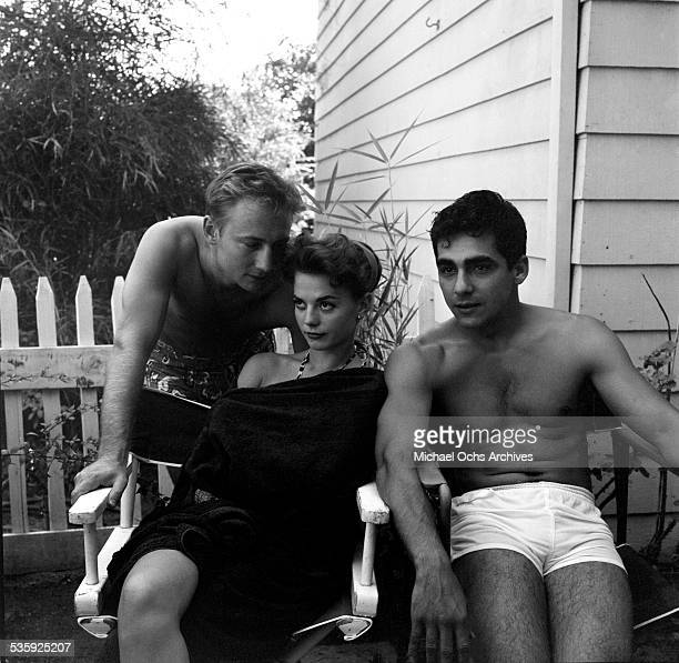 Actress Natalie Wood sits with actors Nick Adams and Perry Lopez and has a pool party in Los AngelesCA