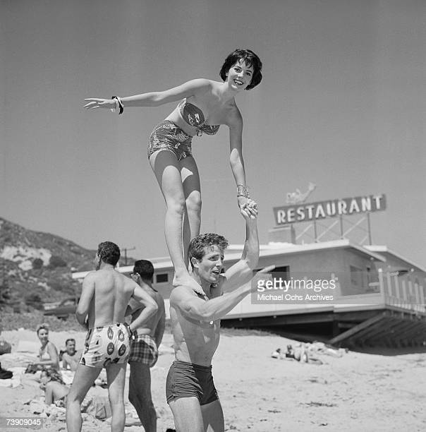 Actress Natalie Wood stands on the shoulders of actor Steve Rowland at the Thalians Beach Ball which was held at the home of Elaine Stewart on July...