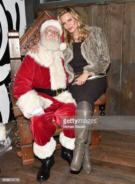 Actress Natasha Henstridge and Santa at Not For Sale x Z Shoes Benefit at Estrella Sunset on December 9, 2016 in West Hollywood, California.