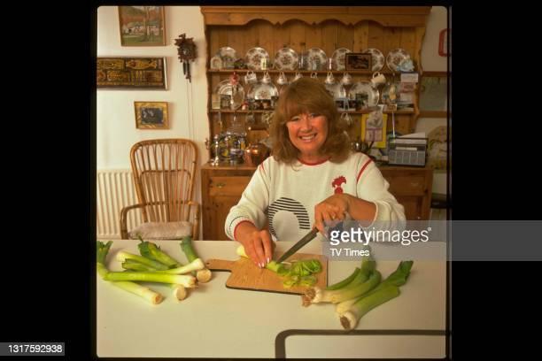 Actress Nerys Hughes photographed cooking at home, circa 1988.