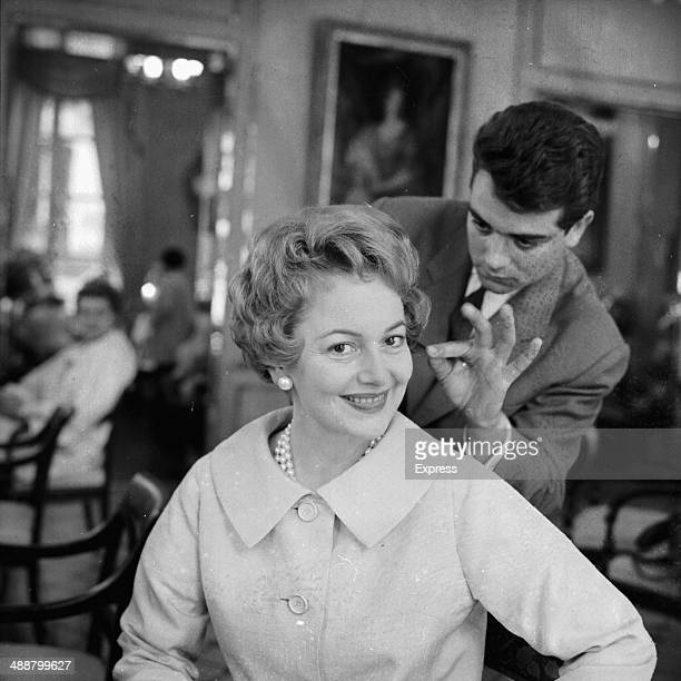 Actress Olivia de Havilland getting her hair and makeup done 1958