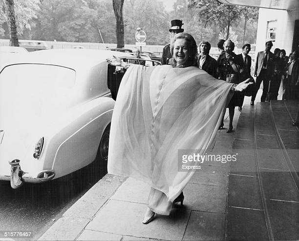 Actress Olivia de Havilland posing for photographers wearing a Dior dress as she leaves the Dorchester Hotel in London England August 24th 1971