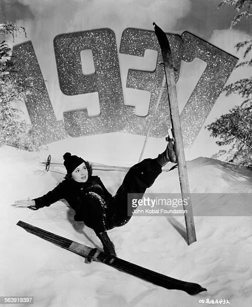 Actress Olivia de Havilland pretending to fall over on a model ski slope in a New Years portrait for Warner Bros Studios 1937