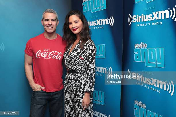 Actress Olivia Munn poses for a photo with SiriusXM host Andy Cohen during a visit to SiriusXM's 'Radio Andy' at the SiriusXM Studios on May 23 2018...