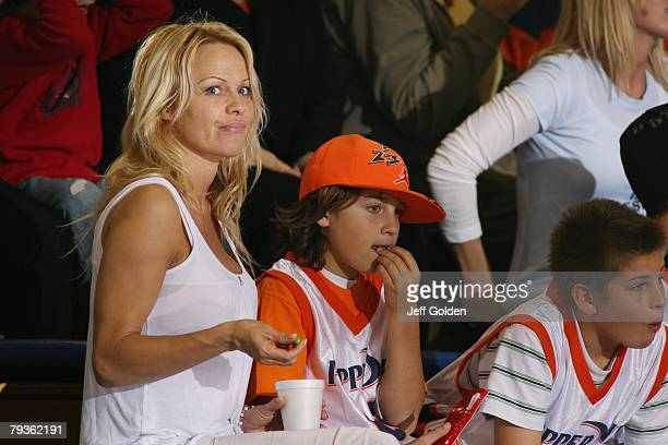 Actress Pamela Anderson eats Skittles as she sits with her son Brandon Thomas Lee before the basketball game between the Loyola Marymount Lions and...