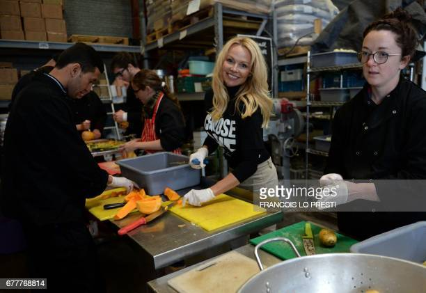 TOPSHOT US actress Pamela Anderson helps prepare food at a distribution center for migrants in Calais on May 3 2017 / AFP PHOTO / FRANCOIS LO PRESTI