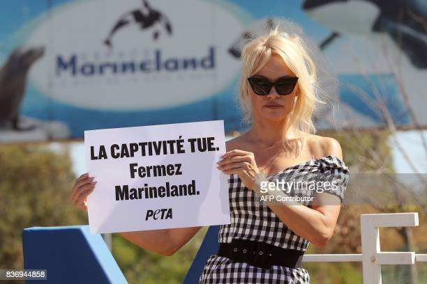 US actress Pamela Anderson holds a placard reading captivity kills shut down Marineland in front of French marine park Marineland on August 22 2017...