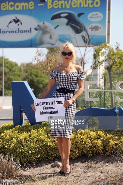 US actress Pamela Anderson holds a placard reading 'captivity kills shut down Marineland' in front of French marine park Marineland on August 22 2017...