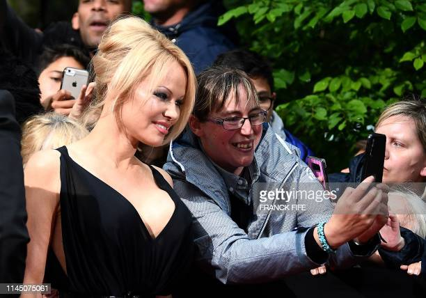 TOPSHOT US actress Pamela Anderson poses for fan as she arrives to take part in a TV show on May 19 2019 in Paris as part of the 28th edition of the...