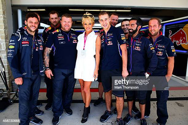 Actress Pamela Anderson poses with members of the Infiniti Red Bull Racing team outside the garage before qualifying for the United States Formula...
