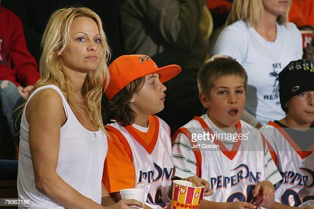 Actress Pamela Anderson sits with her son Brandon Thomas Lee before the basketball game between the Loyola Marymount Lions and the Pepperdine Waves...