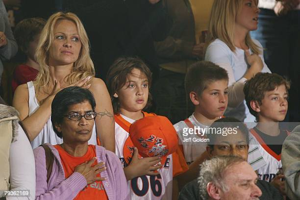 Actress Pamela Anderson stands with her son Brandon Thomas Lee for the singing of the National Anthem before the basketball game between the Loyola...