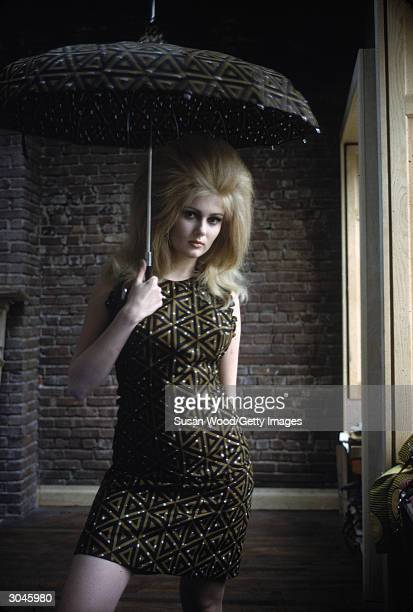 Actress Pamela Tiffin poses in a green and black dress with a triangular pattern and holds a matching umbrella April 1966