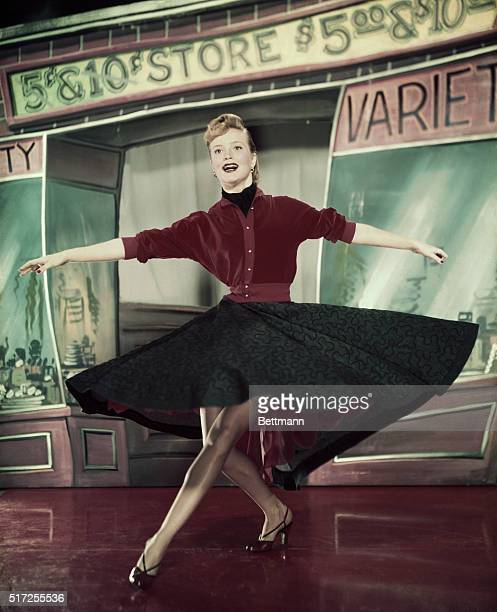 Actress Pat Wymore dancing with swirled dress and also waist up posed smiling