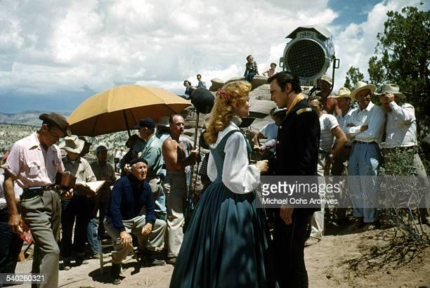 Actress Patrice Wymore on set while director William Keighley watches as a film crew films the movie Rocky Mountain on location in Gallop New Mexico...