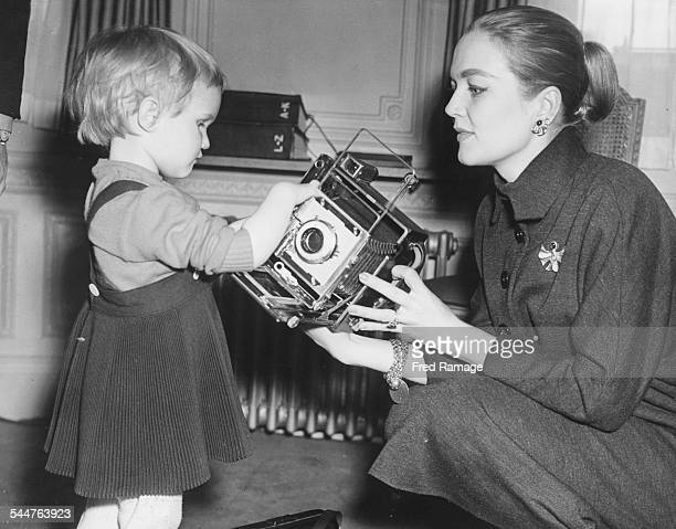 Actress Patrice Wymore showing her young daughter Arnella a camera while London to film 'The Errol Flynn Theatre' in their room at the Savoy Hotel...