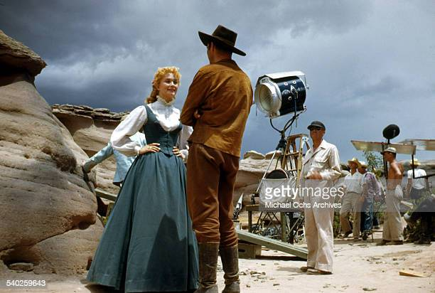 Actress Patrice Wymore talks with actor Errol Flynn on set as a film crew films the movie Rocky Mountain on location in Gallop New Mexico Starring...
