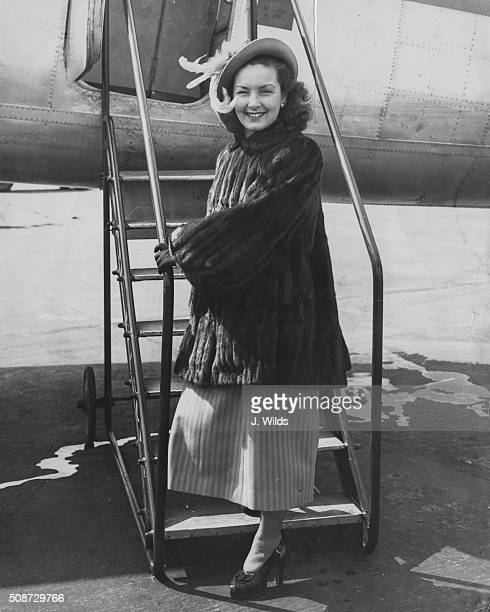 Actress Patricia Roc pictured wearing a fur coat and a feather hat as she boards a plane to meet her husband in Paris at London Airport May 28th 1949