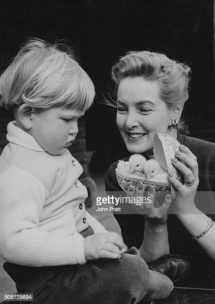 Actress Patricia Roc presenting her young don Micky with two chicks in a toy egg as an Easter gift at her sisters home in Maidenhead England circa...