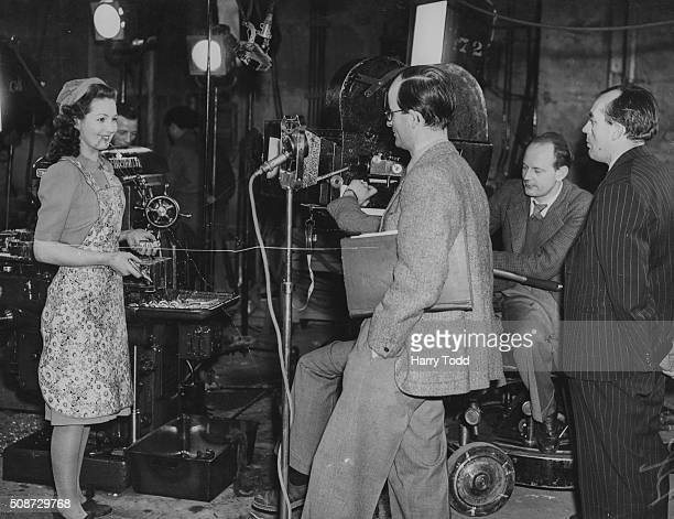 Actress Patricia Roc talking to directors Frank Launder and Sidney Gilliat on the set of the film 'Millions Like Us' at GaumontBritish Studios...