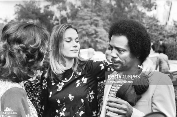 Actress Peggy Lipton puts her arm around the shoulders of music producer Quincy Jones as he talks to another woman at Dean Martin's home in Bel Air...